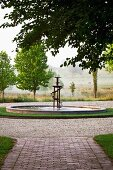 Atmospheric view of landscape with artistic fountain and paved garden path