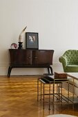 Minimalist, retro living room furnishings with sideboard and nest of delicate tables on herringbone parquet floor