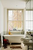 Narrow bathroom with free-standing bathtub and twin sinks in historical English town house with lattice window