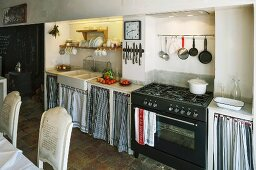 Simple kitchen counter with curtains on base units flanking gas cooker