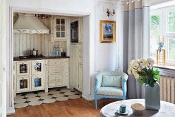 Vase of white roses on table; open doorway with view into shabby-chic kitchenette in background