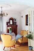 View through open door into lounge area; period armchair and sofa with pale golden silk upholstery with ornamental pattern