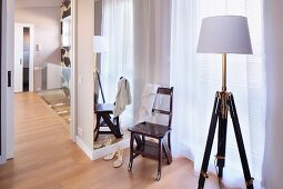 Standard lamp with retro, wooden tripod base and white lampshade and vintage wooden chair in front of window with floor-length, translucent curtain