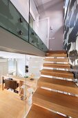 Staircase with pale, solid wood treads, glass partition and view into interior with open-plan kitchen area