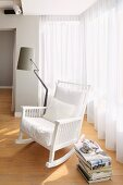 White, wooden rocking chair with white cushions and standard lamp with grey lampshade in front of floor-length, translucent curtains on windows