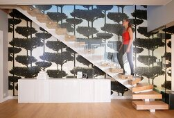 Woman walking up staircase with solid wooden treads and glass balustrade above white sideboard against wallpaper with pattern of trees
