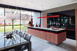 Dining area in front of kitchen area with island counter below delicate red pendant lamp and fitted cupboards with black fronts; glass wall with view into courtyard