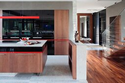 Detail of open-plan kitchen area, island counter with wooden base unit below red strip light in modern interior