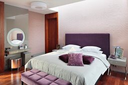 Elegant bedroom; double bed with purple upholstered headboard, scatter cushions in shades of purple on pale grey blanket, minimalist dressing table and silver-coloured stool