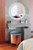 Minimalist dressing table and silver-coloured stool in front of pale grey glass panel with integrated round mirror