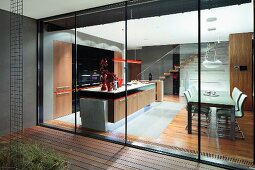 View from terrace through sliding glass wall into illuminated kitchen-dining area in contemporary house