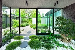 Indoor garden in vestibule with ground-cover plants and tree amongst white pebbles and view of garden through glass facade