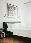 Double bed with grey upholstered headboard, white bed linen and Tolomeo wall lamps flanking framed picture