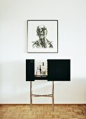 Minibar with black sliding doors on chrome frame below contemporary drawing on wall