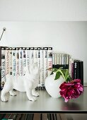 White china dog next to deep pink peony in vase in front of collection of books on stainless steel surface