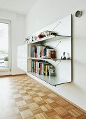 Wall-mounted unit with combination of open shelves and cabinets in modern interior with polished mosaic parquet floor