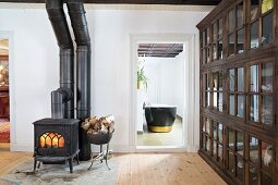 Black wood-burning stove, firewood container and glass-fronted lattice cabinet in simple living room with open interior door and view of bathtub
