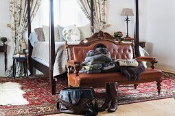 Bag and boots in front of antique bench with brown leather upholstery and carved wooden frame