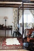 White animal-skin rug on Oriental rug next to wood-framed bed in traditional bedroom with wood-beamed ceiling