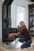 Woman putting firewood into wood-burning stove in rustic living room