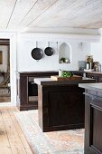 Free-standing island between dark wooden kitchen counters in rustic kitchen with wooden ceiling
