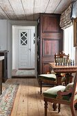 Antique upholstered chairs and chess table next to window in rustic interior with wooden floor and ceiling