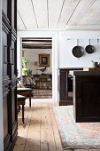 Free-standing dark-wood counter in kitchen with view into adjacent room through open door