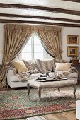 Ottoman with curved legs on Oriental rug, sofa below lattice window with draped curtains