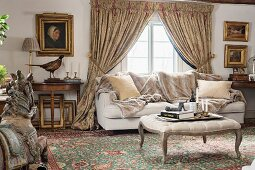 Rococo-style ottoman with curved legs, sofa and antiques in front of window with draped curtains in rustic parlour