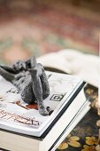 Reclined nude figurine made from dark metal on top of book