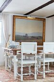 White-framed dining chairs with turned legs around dining table below gilt-framed landscape painting