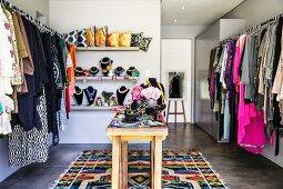Walk-in feminine wardrobe with jewellery racks on narrow wooden table in modern interior