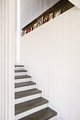 Staircase with concrete treads, white risers and narrow recess in wall decorated with framed photographs