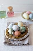 Eggs in pastel colours in Easter nest