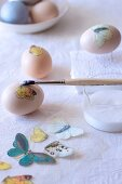 Decorating eggs - applying decoupage butterfly motif using glue