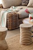 Wicker sofa with beige upholstery, wooden coffee table and wooden stool on sisal rug