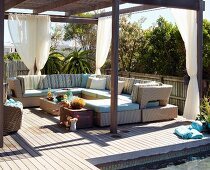 Roofed lounge area with outdoor furniture on wooden terrace in summer sun