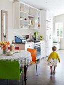 Little girl in light-flooded kitchen with easy-care concrete floor, open-fronted wall cabinets and round dining table with brightly coloured chairs