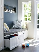 Bench with grey seat cushion, scatter cushions and drawers for storing toys in niche next to window