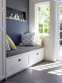 Bench with grey seat cushion & scatter cushions and storage drawers in niche next to window