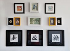 Framed initials in black frames below small pictures of animals and badges on wall