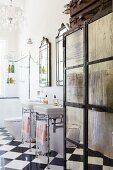 Vintage metal cupboard with mirrored panels next to twin washstands on metal frames on glossy chequered floor