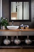 Modern washstand with white basin, three metal vases on shelf below and framed mirror on grey, marbled wall