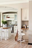 Small workspace integrated in niche next to white, open-plan, country-house kitchen