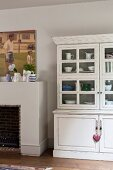 White, vintage dresser with glass-fronted top section next to open fireplace