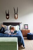 Boy reading on bed below two hunting trophies on wall
