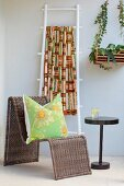 Cushion on curved rattan chair next to side table and brightly-coloured ethnic textile hanging over white-painted ladder leaning against wall