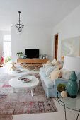 Coffee table with white, amorphous top and pale blue sofa in eclectic, spacious living room
