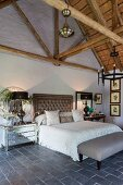 Double bed with button-tufted headboard in elegant, vintage bedroom with exposed roof structure