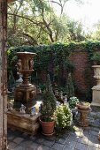 Antique fountain and planters in rustic courtyard with climber-covered brick wall in background